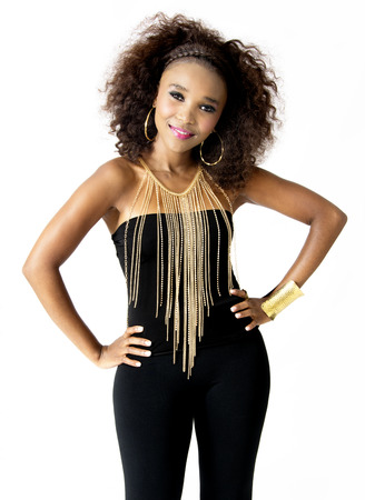 Beautiful African Female Model with Hands on Hips,  Afro Hairstyle, Wearing Tight Black Clothes, and Golden Jewellery, Isolated on White Background