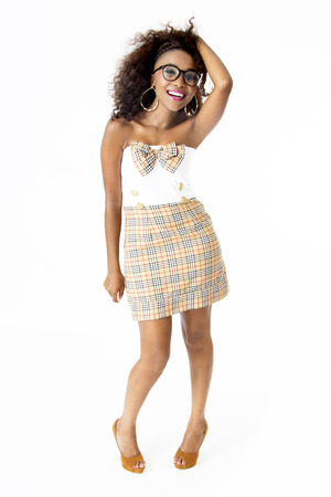 Full-Length Picture of Beautiful, Happy African Female Model Wearing Cute Tartan Dress with a Bow, Big Afro Hairstyle, Spectacles, with a Big Smile, Isolated on White Background