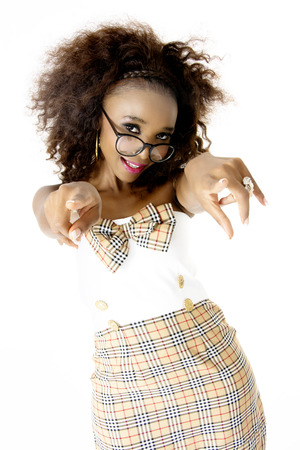 Beautiful African Female Model Wearing a Tartan Dress with a Bow, Pink Lips, Spectacles, Pointing Towards You with Both Hands, Isolated on White Background