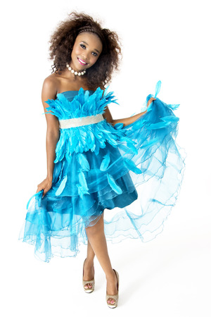 Full-Length Picture of Beautiful African Female Model in Playful Mood, Wearing Turquoise Feathered Designer Dress, Silver Shining Belt, Big Afro Hairstyle, White Beaded Necklace, Isolated on White Background Stock Photo
