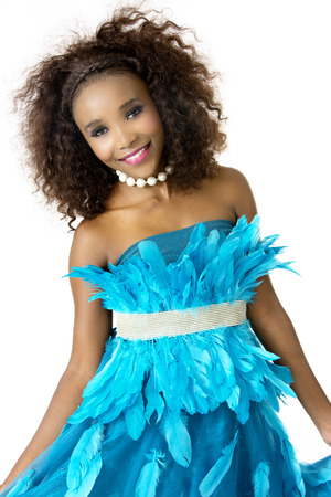 feathered: Beautiful African Female Model in Playful Mood, Wearing Turquoise Feathered Designer Dress, Silver Shining Belt, Big Afro Hairstyle, White Beaded Necklace, Isolated on White Background