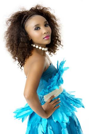 feathered: Beautiful African Female Model, Wearing Turquoise Feathered Designer Dress, Silver Shining Belt, Big Afro Hairstyle, White Beaded Necklace, Sideways Shot, Isolated on White Background Stock Photo