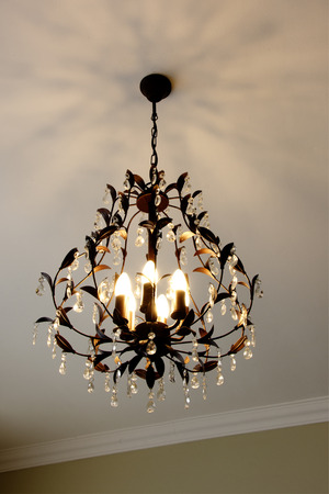 Beautiful Metal Chandelier with Floral Decorations, Crystals, and Multiple Bulbs Stock Photo