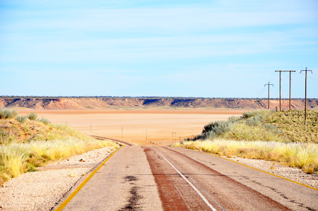 Traveling along a scenic tar road through a dry Koopan South Africa Africa Stock Photo
