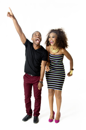 FullLength Picture of Attractive African Couple Dancing Shouting and Laughing Together in the Studio Male Model Pointing Up Isolated on White Background photo
