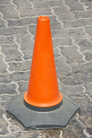 empedrado: Primer plano de cono de tráfico naranja único en un camino pavimentado