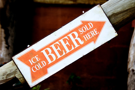 Closeup of an Orange and White Sign indicating the Direction to the Bar, Upstairs - Ice Cold Beer Sold Here Stock Photo