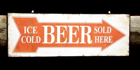 Closeup of an Orange and White Sign indicating the Direction to the Bar - Ice Cold Beer Sold Here