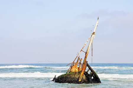 Rusted Old Shipwreck in the the Shallow Waters off the Coast of Angola, Southern Africa Stock Photo