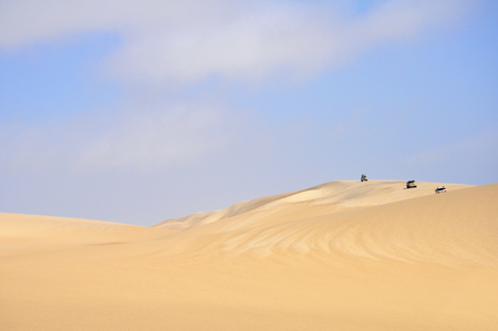 Three Vehicles Enjoying and Adventurous Drive Across the Sand Dunes in the Desert of Angola, Southern Africa Stock Photo