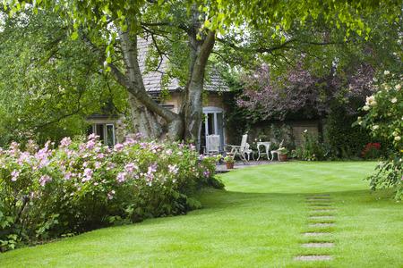 Inglés Cottage Garden, con pequeño patio, en verano Editorial