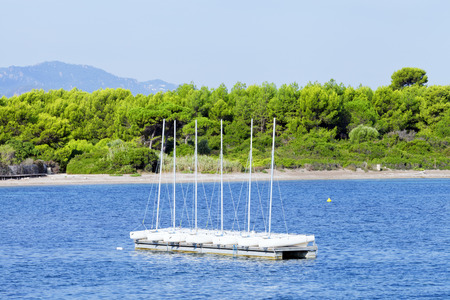 Small sailing boats on a sea platform close to shore, beach .