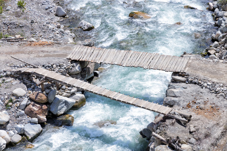 Top view of two old wooden bridges spanning over fast flowing mountain river Фото со стока