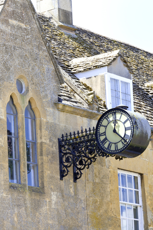 Victorian aged Double Sided Hanging Wall Clock with Roman numerals on a side of old village building