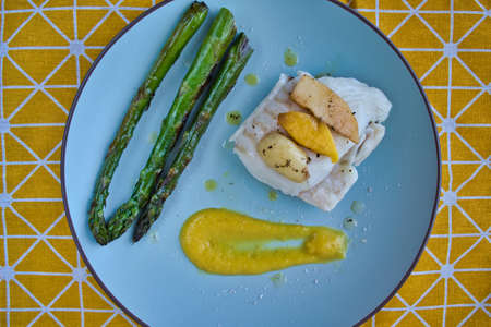 Top view of hake fillet with mango sauce and asparagus. Plate with warm colors and yellow background. Seafood dish