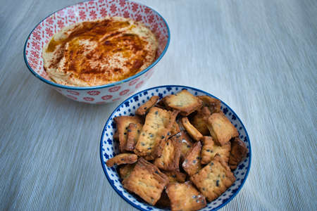homemade chickpea humus with red pepper and bread sticks crunchy for dipping served in a bowl
