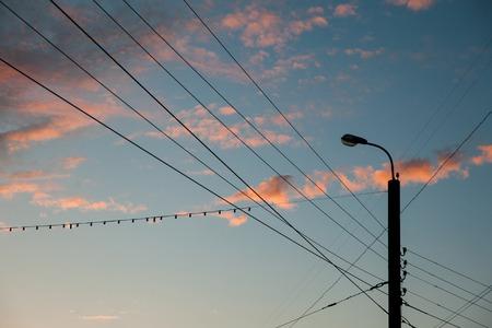 Silhouette der Stadt der Lichter und Drähte bei Sonnenuntergang mit blauem Himmel amd rosa Wolken