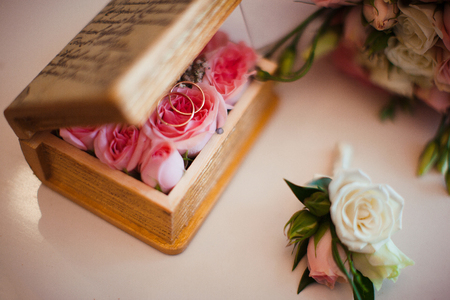 flower box: wooden flower box with gold wedding rings and pink roses on a white surface Stock Photo