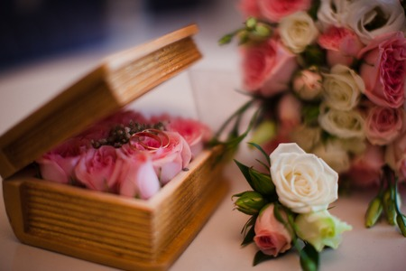 flower box: wooden flower box with gold wedding rings and pink roses
