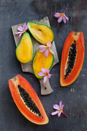 papaya flower: Overhead still life of fresh and juicy tropical fruits on a dark shabby background. Vegan food: three slices of yellow mango and orange papaya with black seeds cut lengthwise into two halves. Stock Photo