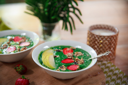 Healthy vegan food concept: green smoothie bowl with spinach, spirulina, pear and red strawberry topped with raw superfood granola. Vegetarian bright breakfast.