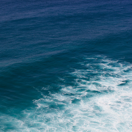 Indian ocean texture. Turquoise sea water with white foam. Powerful and peaceful nature concept.