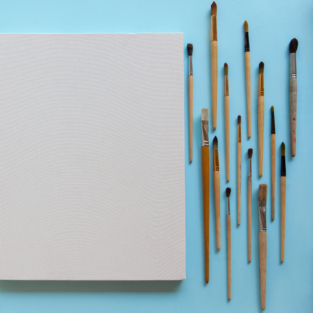 Textured blank white canvas and a lot of different sizes brushes for painting on pastel blue paper background with copy space. Drawing education for beginners and inspiration concept.