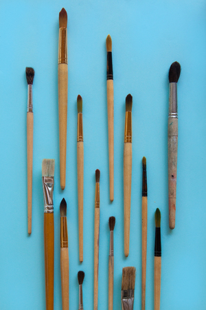 A lot of different sizes brushes for painting on bright blue paper background. Drawing education and inspiration concept. Stock Photo