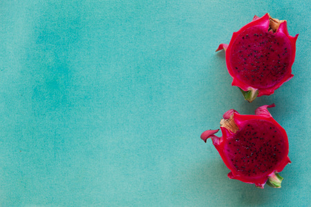 Colorful minimalistic still life of two halves red dragon fruit on a bright blue textured background. Vegan healthy food concept. Contrast tropical fruit horizontal background with copy space.