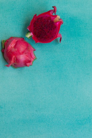 Colorful minimalistic still life of two halves red dragon fruit on a bright blue textured background. Vegan healthy food concept. Contrast tropical fruit vertical background with copy space.