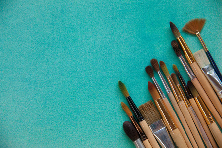 A lot of different sizes brushes for painting on bright blue textured watercolor canvas background with copy space. Drawing education and inspiration concept.