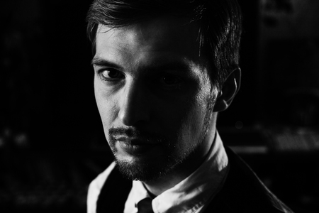 Black and white dramatic portrait of a handsome confident man, 30-35 years old. Strong face looking to the camera, half face in shadow. Serious headshot photo.