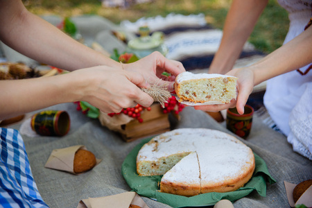 Summer picnic outdoor. Bright and colorful hipster lunch in the park. Female hands cut a piece of pie Stock Photo