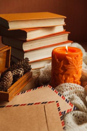 큰 오렌지 촛불, 책 및 소나무 범프의 상자의 더미의 아늑한 아직도 인생. 스톡 콘텐츠 - 86141194
