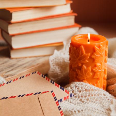 큰 오렌지 촛불, 책 및 빈티지 크 래 프 트 봉투의 더미의 아늑한 아직도 인생. 스톡 콘텐츠 - 86141195