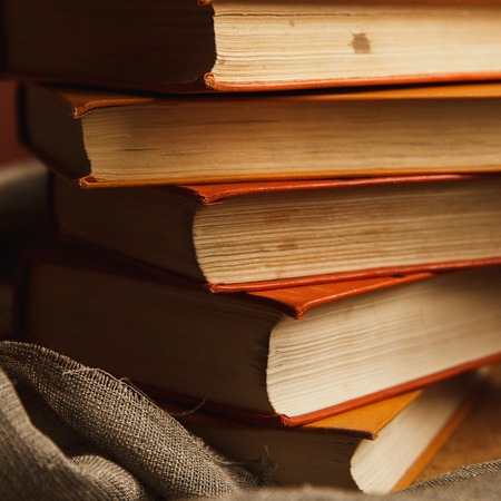 A stack of paper books in orange color on textured wooden surface. Autumn mood concept. Time to read. 스톡 콘텐츠