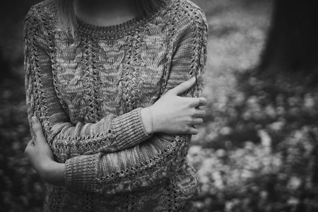 Girl in knitted sweater with crossed hands. Black and white sad background. Unconfident woman dramatic concept. Stock Photo