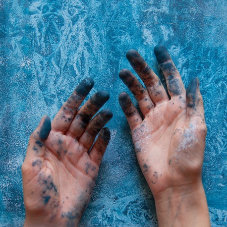 Dirty painted female hands on background of colorful background. Creativity drawing concept. Stock Photo