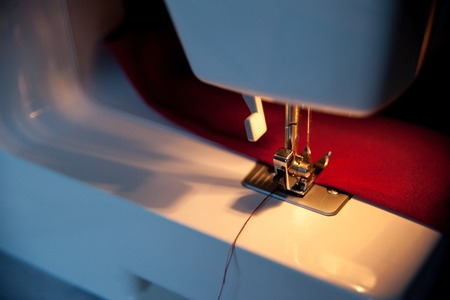 Sewing hobby background. Sewing machine with red fabric. Close up process with copy space. Dramatic dark colors. Stock Photo