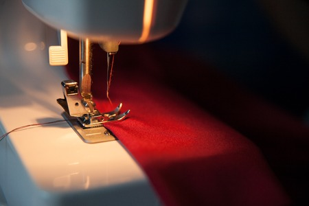 Sewing hobby background. Sewing machine with red fabric. Close up process with copy space. Dramatic dark colors. Stok Fotoğraf