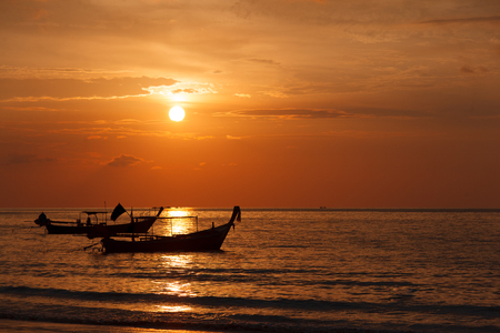 Two longtail boat silhouette at sunset in Phuket, Thailand. Tropic travel destination. Meditative and simple seascape with copy space. Stock Photo