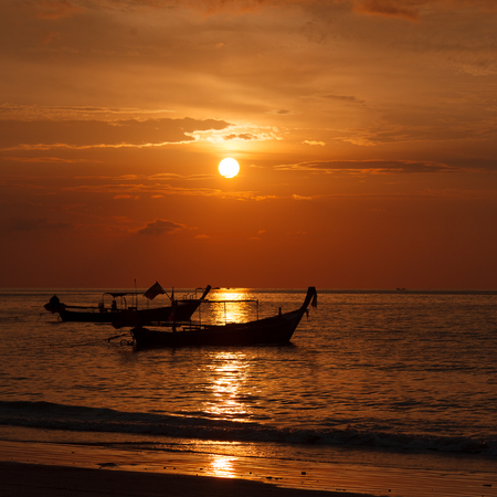 Two longtail boat silhouette at sunset in Phuket, Thailand. Tropic travel destination. Meditative and simple seascape.