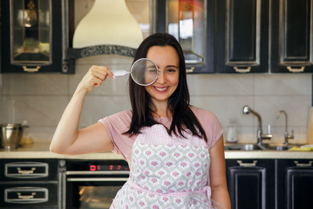 Plump woman cooking on the kitchen. Mature woman in pastel apron covers her eye with metal sieve and smiling.