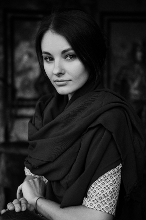 Black and white vertical portrait of young beautiful woman indoor. Strict girl with stern look Stock Photo