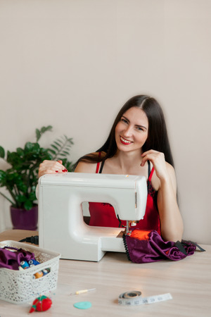 An attractive young woman sits at a table and sews silk underwear on a sewing machine. Concept of female small business at home.