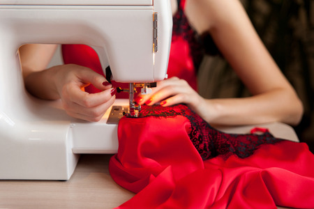 Female hands on sewing machine. Process of silk lingerie making. Close up of seamstress work. Banco de Imagens - 90451379