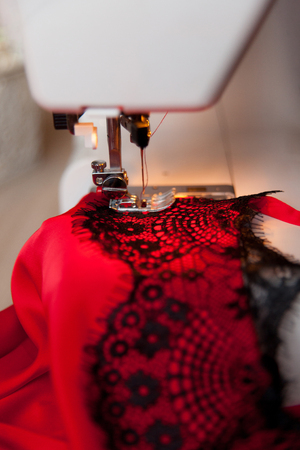 Red silk top with black laces lies on a sewing machine. Process of sensual lingerie making.