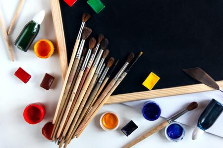 Tekengereedschappen, verven en penselen liggen op een leeg bord. Het concept creativiteit en onderwijstekening. Bovenste stilleven met kopie ruimte.