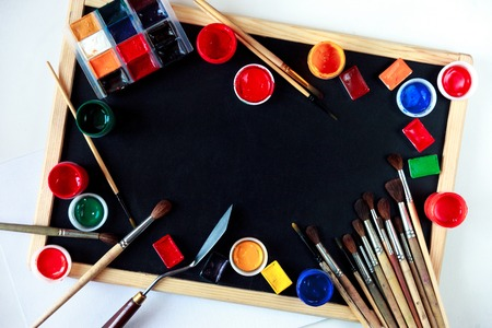 Drawing tools, paints and brushes lie on an empty chalkboard. The concept of creativity and teaching drawing. Overhead still life with copy space.