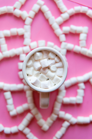 Flat lay cup of cacao with mini marshmallows on pink paper background. Candys lies in shape of mandala. Stock Photo